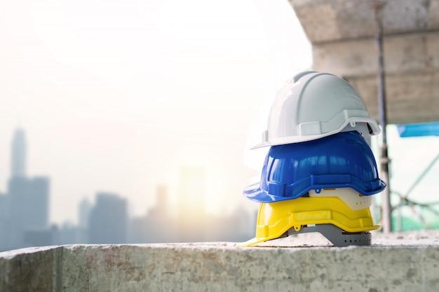 Żółty, niebieski i biały kask kask budowlany pracujący na stole cementowym w górnej części budynku pokładu i muru miejskiego