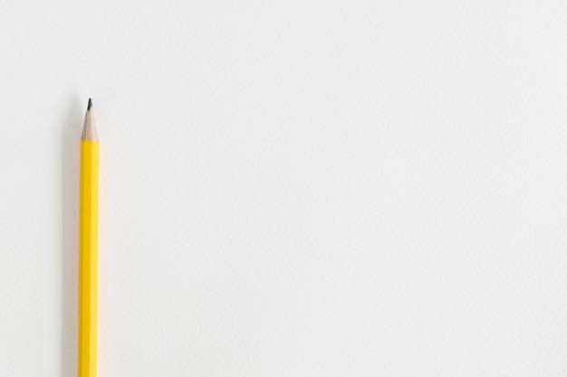 Żółty ołówek na białym papierze do rysowania z miejsca na kopię