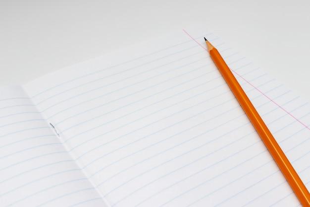 Żółty ołówek na tle biały prążkowany prześcieradło notatnik