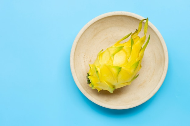 Żółty owoc pitahaya lub smoka na talerzu na niebieskim stole