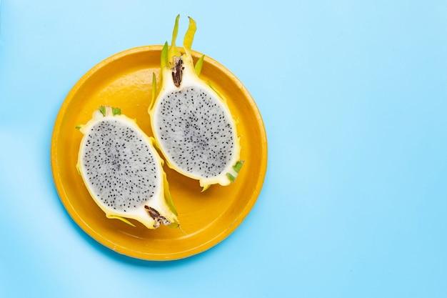 Żółty owoc pitahaya lub smoka na żółtym talerzu na niebieskim tle. skopiuj miejsce