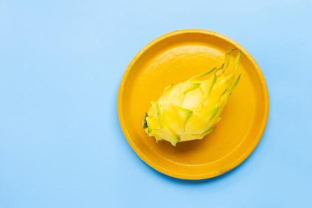 Żółty owoc pitahaya lub smoka na żółtym talerzu.