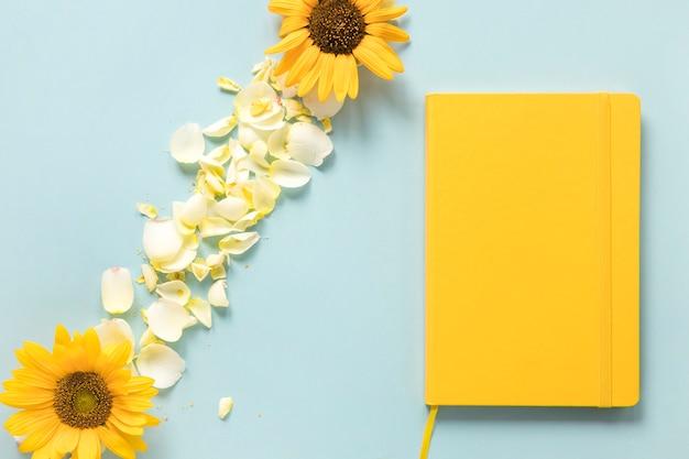 Żółty pamiętnik blisko słoneczników i płatków na niebieskim tle