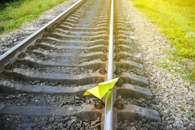 Żółty papier czerpany samolot leżący na torach kolejowych. zdjęcie koncepcji wolności. motywacja stylu życia podróży. branża transportu kolejowego.