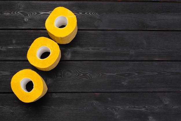 Żółty papier toaletowy na czarnym drewnianym stołowym odgórnym widoku