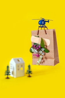 Żółty papierowej torby kwiatu toyhelicopter lata błękitnego tła doręczeniowego domu drzewa