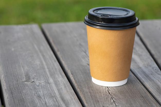 Żółty papierowy kubek do kawy na drewnianej powierzchni do kawy i usług.