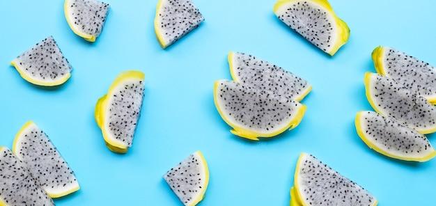 Żółty pitahaya lub plastry owoców smoka na niebieskim tle.