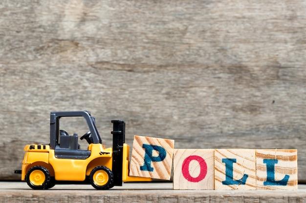 Żółty plastikowy wózek widłowy chwyta list p uzupełniać sondaż na drewnianym tle
