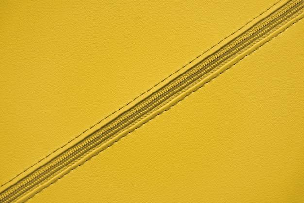 Żółty plastikowy zamek błyskawiczny na skórzanym materiale. tło ubrania i akcesoria. ukośny zamek błyskawiczny.