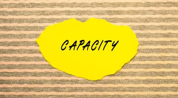 Żółty podarty papier z napisem capacity na szaro-różowej powierzchni