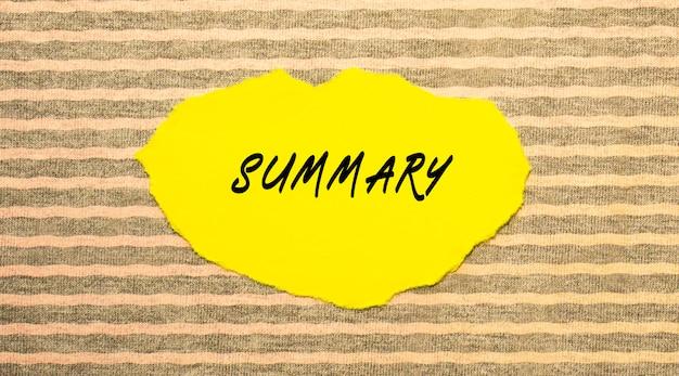 Żółty podarty papier z napisem podsumowanie na szaro-różowym tle. widok z góry.