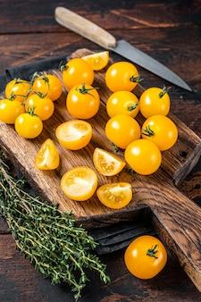 Żółty pomidorek cherry krojone na drewnianą deskę do krojenia. ciemne drewniane tło. widok z góry.