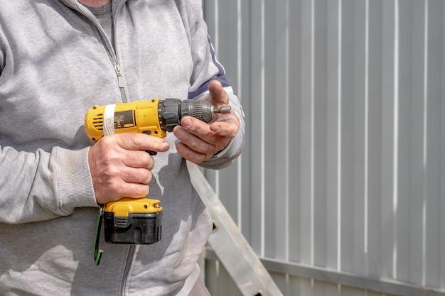 Żółty porysowany wkrętak akumulatorowy w męskich rękach ciała modzelowatego