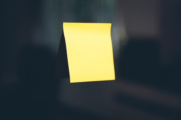 Żółty post-it zatrzymany na czarnej ścianie
