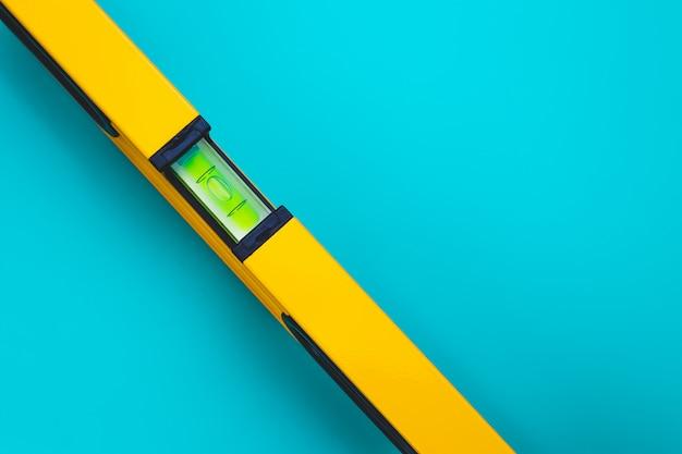 Żółty poziom narzędzie na niebieskim tle. rurowa poziomica alkoholowa. przestrzeń tekstowa.