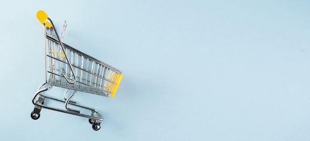 Żółty pusty mini koszyk na pastelowym niebieskim tle. koncepcja zakupów.