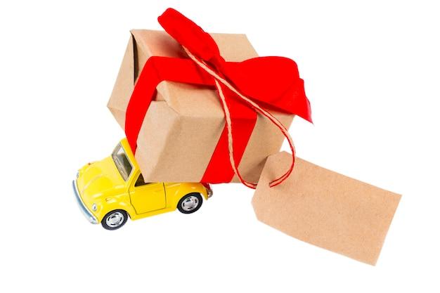 Żółty retro zabawka samochód dostarczający pudełko na prezenty z tagiem z pustym miejscem na tekst na białym tle.