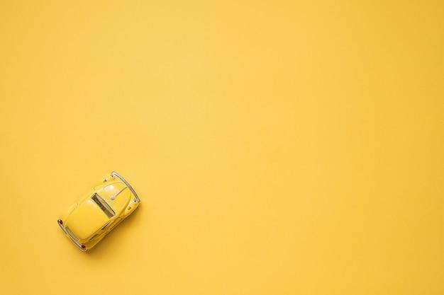 Żółty. retro zabawka samochód na żółtym .. koncepcja podróży latem. taxi. widok z góry.