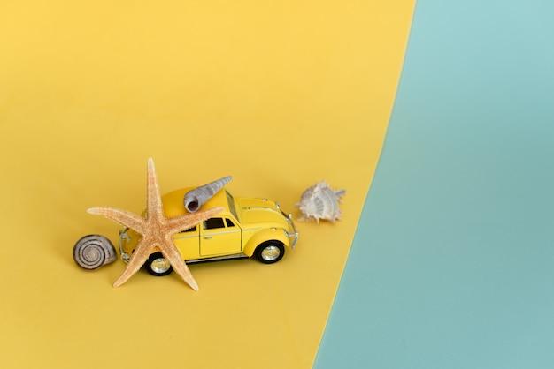 Żółty retro zabawkarski samochód na kolorze żółtym