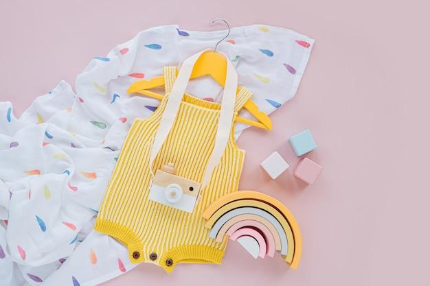 Żółty romper z dzianiny na wieszaku z zabawkowym aparatem i drewnianymi zabawkami. zestaw ubranek i akcesoriów dla niemowląt na wiosnę lub lato. moda dla dzieci. płaski układanie, widok z góry
