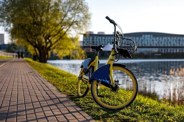 Żółty rower do wypożyczenia w mieście. zachód słońca nad stawem.