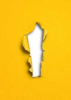 Żółty rozdarty papier z otworem