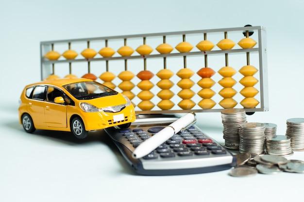 Żółty samochód i długopis na kalkulatorze z żółtym samochodem na kalkulatorze z liczydłem i monetami