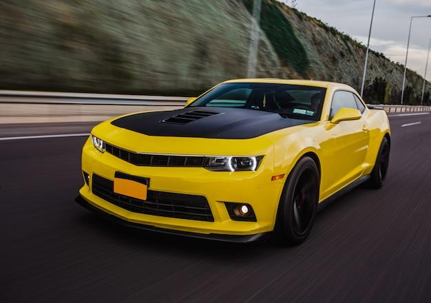 Żółty samochód sportowy z czarnym autotuningiem na drodze.