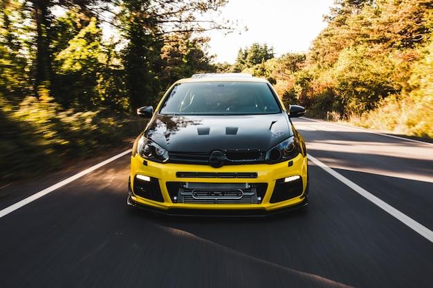 Żółty samochód sportowy z czarnym autotuningiem.