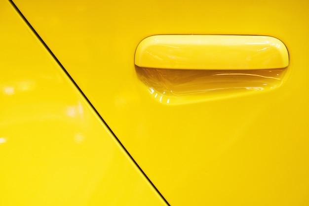 Żółty samochodowy drzwiowej klamki tło