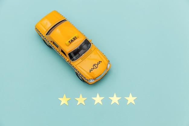 Żółty samochodzik taxi cab i 5 gwiazdek ocena na białym tle na niebieskim tle.