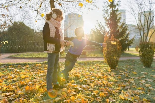 Żółty sezon jesień, dzieci chłopiec i dziewczynka spaceru w parku