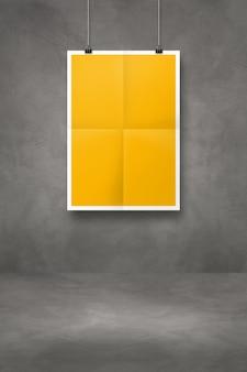 Żółty składany plakat wiszący na ciemnej betonowej ścianie z klipsami. pusty szablon makiety