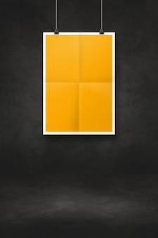 Żółty składany plakat wiszący na czarnej ścianie z klipsami. pusty szablon makiety