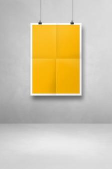 Żółty składany plakat wiszący na czystej ścianie z klipsami. pusty szablon makiety