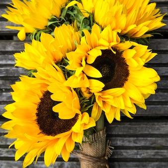 Żółty słonecznikowy bukiet na drewnianym nieociosanym tle