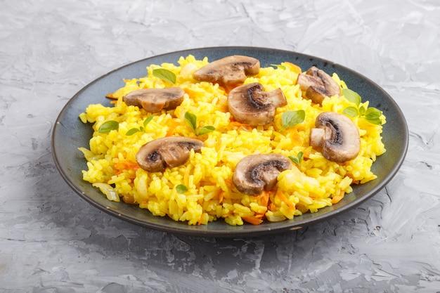 Żółty smażony ryż z pieczarkami grzybami kurkumy i oregano na niebieskim talerzu ceramicznym na szarym tle betonu