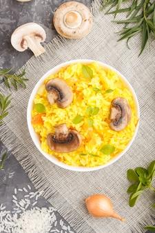 Żółty smażony ryż z pieczarkami grzybami kurkumy i oregano w białej ceramicznej misce na czarnym tle betonowym