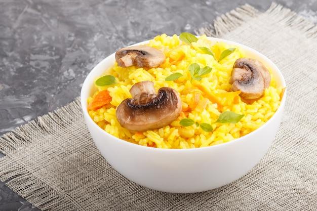Żółty smażony ryż z pieczarkami, kurkumą i oregano w białej ceramicznej misce na czarnym tle betonowym