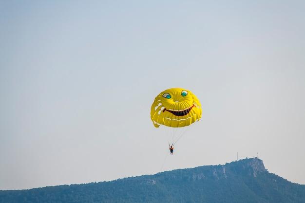 Żółty spadochron z turystą lecącego przez błękitne letnie niebo