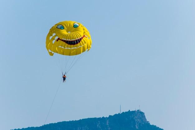 Żółty spadochron z turystą lecący przez błękitne letnie niebo nad górą