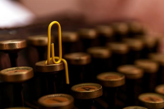 Żółty spinacza do papieru siedzi na maszynie do pisania, z bliska.