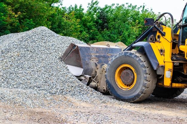 Żółty spychacz ładowarki kołowej pracuje w kamieniołomie