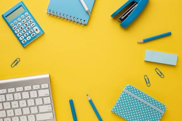 Żółty stół roboczy z klawiaturą, kalkulatorem, notesami, gumką, ołówkiem, pisakiem, zszywaczem i spinaczami do papieru. leżał na płasko