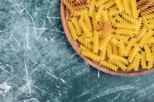 Żółty surowy makaron fusilli na drewnianym talerzu.