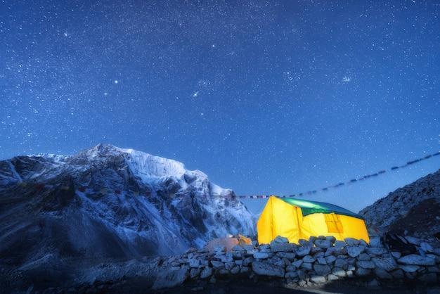 Żółty świecący namiot na tle wysokich skał ze śnieżnym szczytem i niebem z gwiazdami