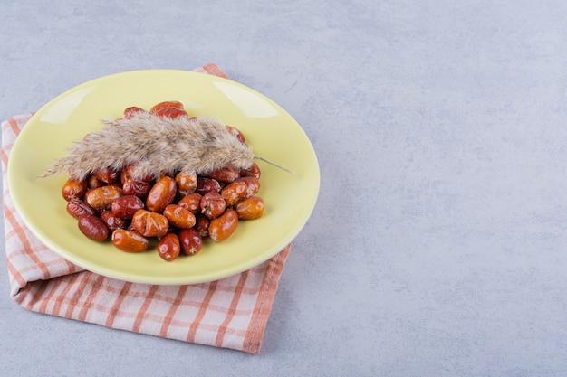 Żółty talerz smaczne dojrzałe srebrne jagody na kamieniu.