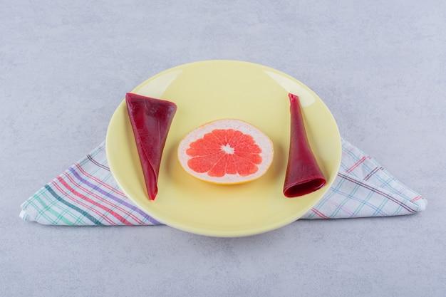 Żółty talerz suchych miąższów owocowych i grejpfruta na kamieniu.