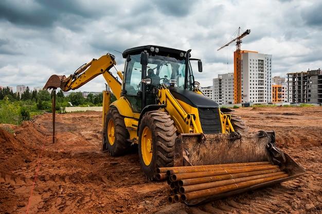 Żółty traktor ustawia słupy w polu pod nową budowę